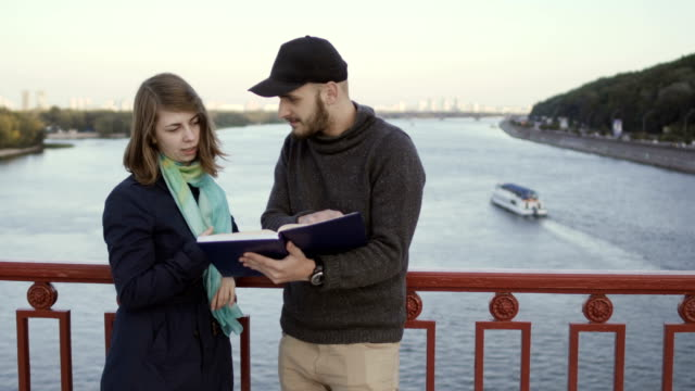 Two friends discuss book at the bridge video