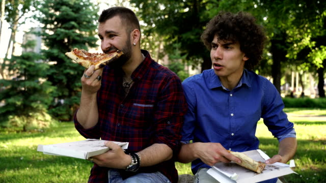 vídeos de stock e filmes b-roll de two friends eating pizza in the park - colesterol