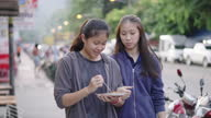 istock Two Friends enjoy shopping and eating in local street while eating some street food 1287908349