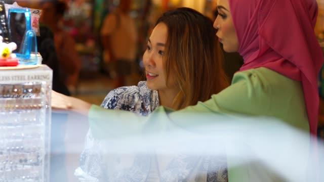 バザーで買い物を持つ 2 人の友人 - マレーシア点の映像素材/bロール