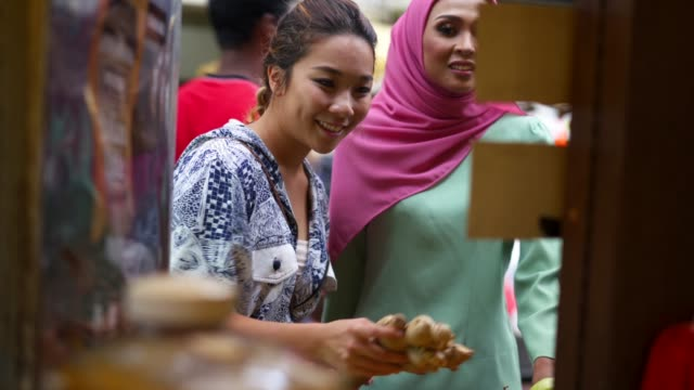 Two friends having shopping at the market together Two friends, one chinese young woman and one muslim mid adult woman,  having shopping at the market together spice stock videos & royalty-free footage