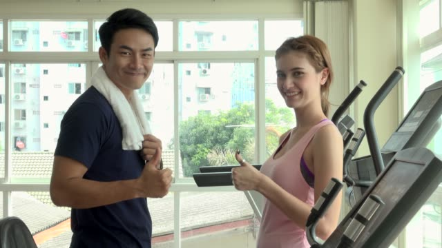 Two Friends In Gym Smile And Look At Camera