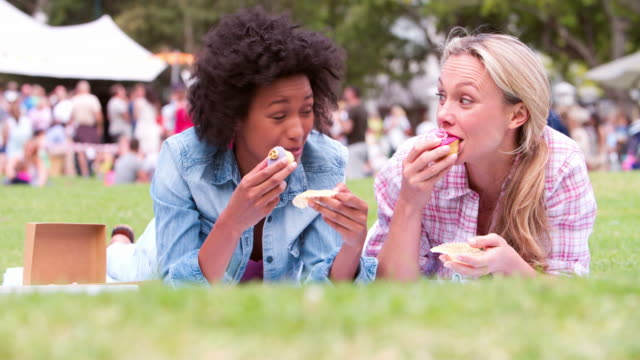 Two friends lying on the grass and eating cakes at an event