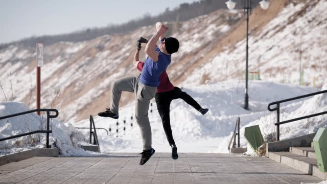 Two friends make a coup in the air, men are engaged in the implementation of professional tricks, they are in nature on a winter day video