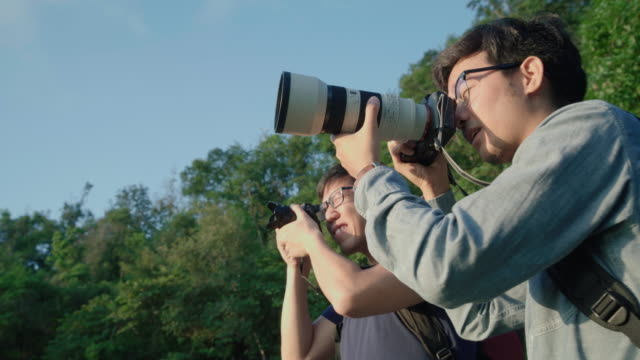 Two friends photographer talking while photograph the sunset view video