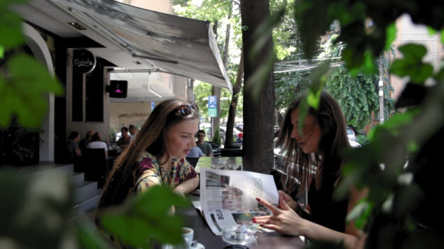 Two friends reading magazine and talking while sitting in cafe