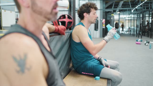 Two friends rest and drink water after practicing at the boxing ring