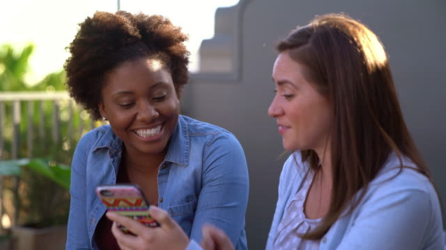 Two friends sat outside at early evening looking at a smartphone video