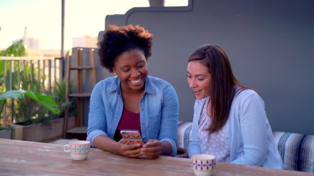 vídeos de stock, filmes e b-roll de dois amigos sentou-se fora no início da noite a olhar para um smartphone - afro americano