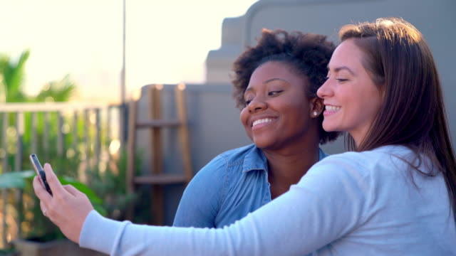 Two friends sat outside at early evening taking selfies - video
