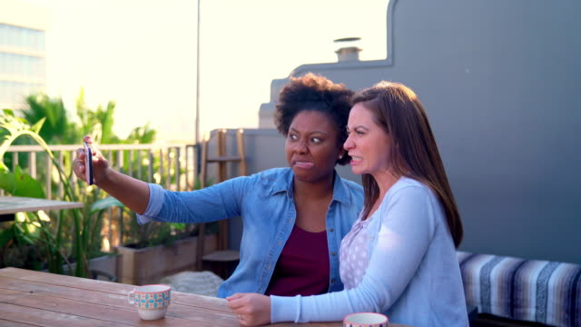 Two friends sat taking selfies outside in the early evening sun - vídeo