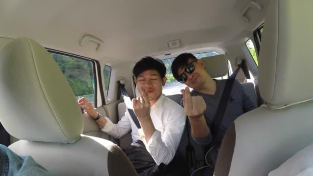 vídeos y material grabado en eventos de stock de dos amigos sentados en el coche listos para empezar las vacaciones - uso compartido del coche