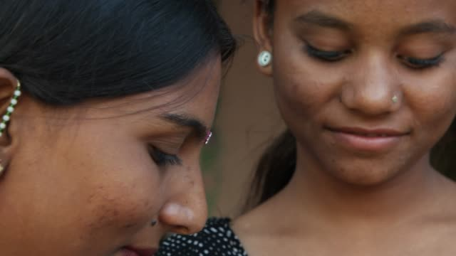 Two friends smiling at discovering something closeup on their pretty faces all ready in their traditional attire and finally pan down to see they are busy with their smart watch in black colour new Women wearing tradition costumes, jewelry and makeup bonding in rural setting in Inda indian culture stock videos & royalty-free footage