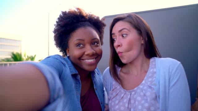 Two friends taking selfies outside video