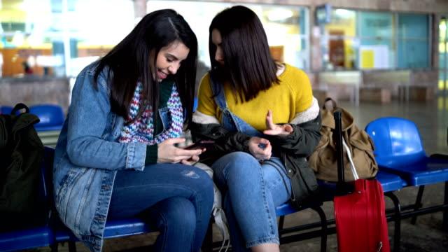 zwei freunde im bahnhof unterhalten und warten - editorial videos stock-videos und b-roll-filmmaterial
