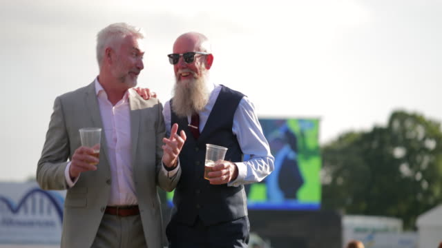 Two Friends Talking At Races Two friends talking and drinking with each other after a fun day at the races. formalwear stock videos & royalty-free footage