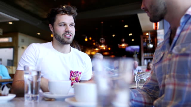 Zwei Freunde in einem Cafe im Gespräch – Video