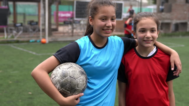 Two friends together on a soccer field video