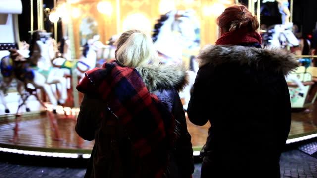 vídeos de stock, filmes e b-roll de dois amigos quer passeio em casar-go-round - moda de inverno