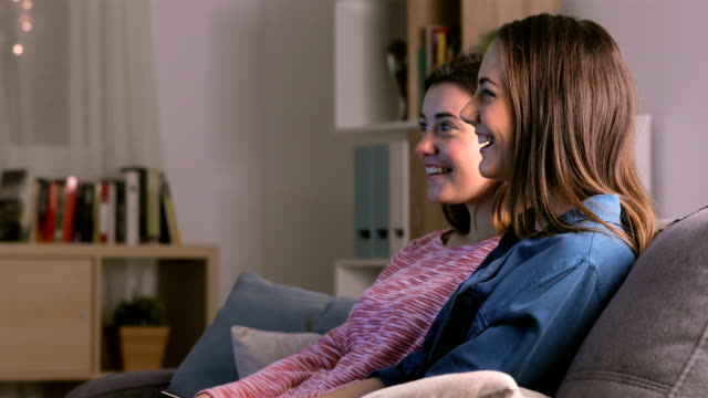 vídeos y material grabado en eventos de stock de dos amigos viendo la televisión en la noche - hermana