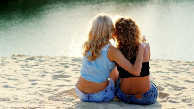Two friends women sitting on the beach, admiring the beautiful scenery video