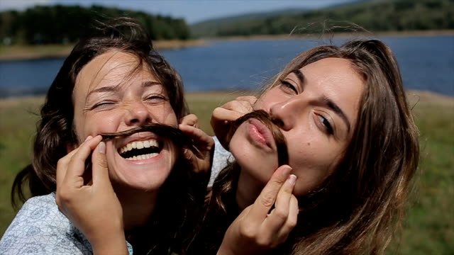 two funny girls make mustache with hair