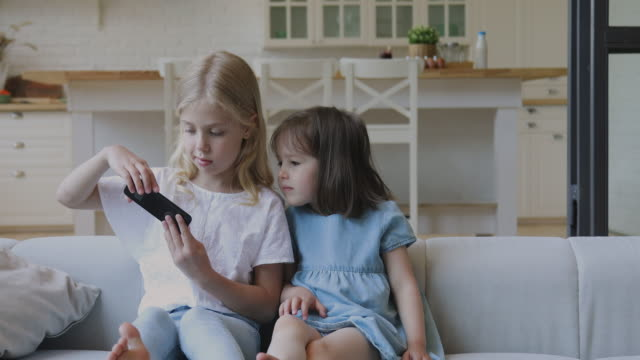 自宅で自分撮りを取るスマートフォンを使用して2面白い子供の姉妹 - 兄弟姉妹点の映像素材/bロール