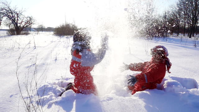 two funny kids throwing snow together - śnieg filmów i materiałów b-roll