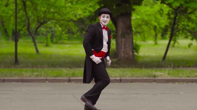 two funny mimes play jokes in the park - гримировальные краски стоковые видео и кадры b-roll