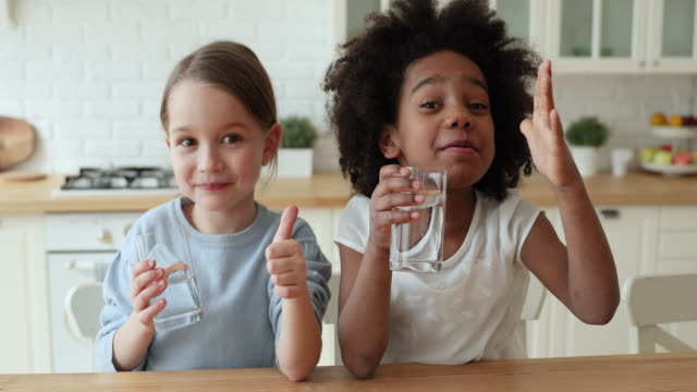 stockvideo's en b-roll-footage met twee grappige gemengde raskinderen die water tonen omhoog duimen tonen - water drinken