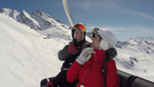Two Funny Skiers Fooling Around Sitting On The Ski Lift In Winter Mountain