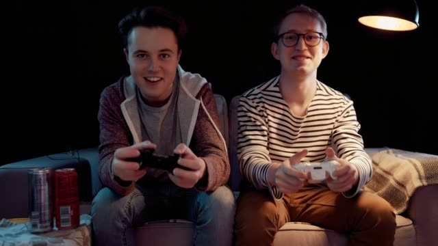 two gamers in front of the screen are cutting in the online battle - развлекательные игры стоковые видео и кадры b-roll
