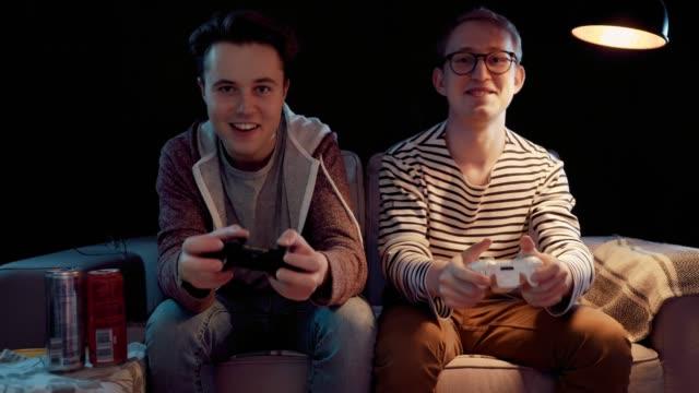 vídeos de stock, filmes e b-roll de os dois jogadores na frente da tela estão cortando na batalha on-line - game