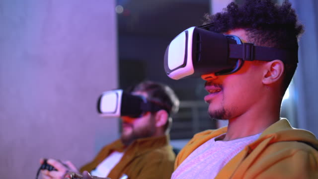 Two gamers playing video game in vr headsets, discussing competition strategy