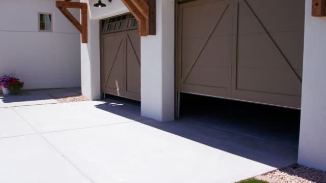 two garage doors open rising view from corner of garage - portoni video stock e b–roll
