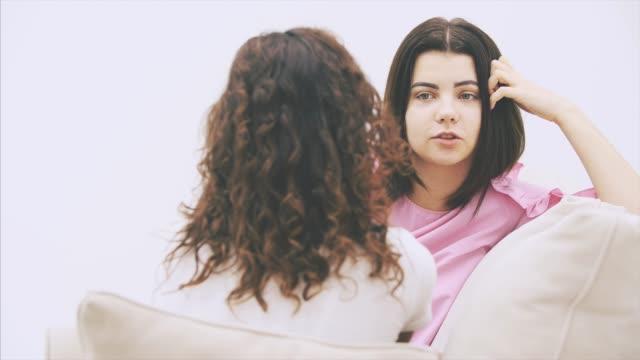 två tjej vänner pratar sittande i soffan i varm hemmiljö. kinky flicka sitter med henne tillbaka till kameran, suddig. - kvinna ventilationssystem bildbanksvideor och videomaterial från bakom kulisserna