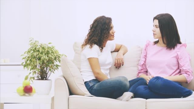två tjej vänner pratar sittande i soffan i varm hemmiljö. - kvinna ventilationssystem bildbanksvideor och videomaterial från bakom kulisserna