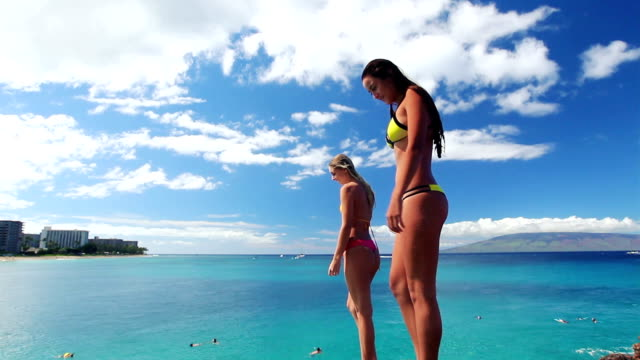 Two Girl Friends Jump Off Cliff into Ocean in Bikinis in Hawaii. video