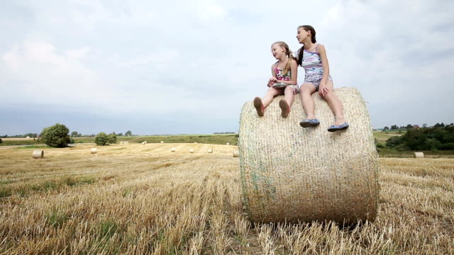 Two girl sits on haystack. video