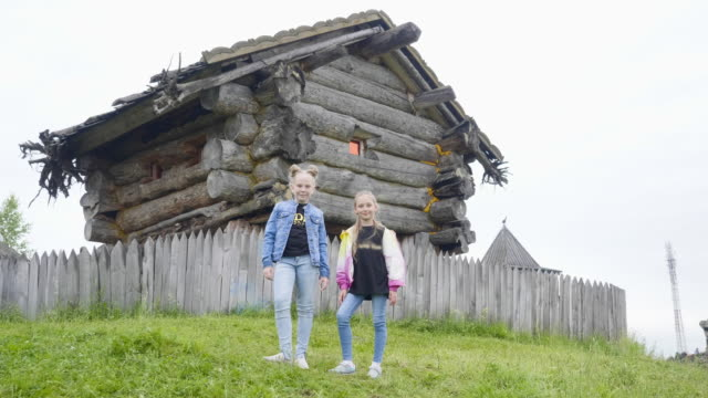 Two girl teenager standing on green lawn on rotating fairy tale house. Teenager girl posing on wooden house of old witch in fairy tale village