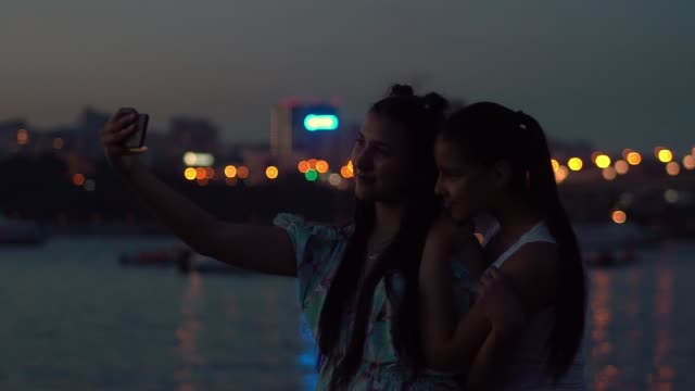 two girlfriends do selfie at night on a background of lights. slow motion - salt lake stan utah filmów i materiałów b-roll