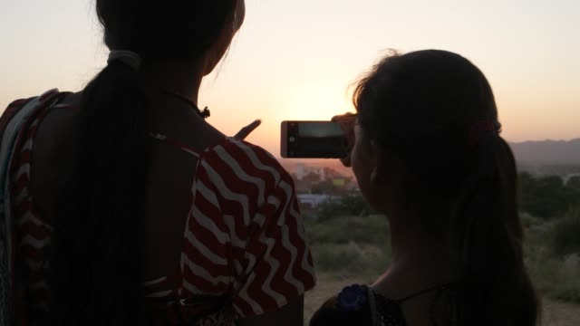 two girlfriends holding hands walk to sunset beautiful vantage point take phone mobile photo video romantic setting in traditional dress silhouette in rajasthan india handheld from behind medium two - sari filmów i materiałów b-roll