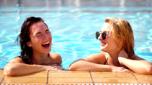 Two girlfriends laugh in pool. Pretty girls spending time on vacations Two girlfriends laugh in pool. Pretty girls spending time on vacations. Enjoying summer. Lifestyle concept. Girls in excellent mood bathing in pool on vacations. Women relaxing girlfriend stock videos & royalty-free footage