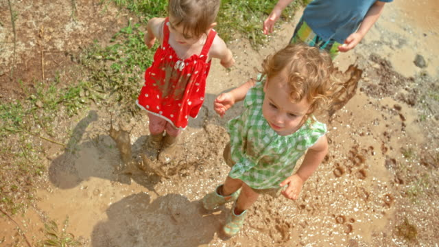 SLO MO Two girls and a boy jumping in the muddy puddle in sunshine