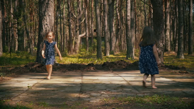 Two girls are dancing in the summer forest video