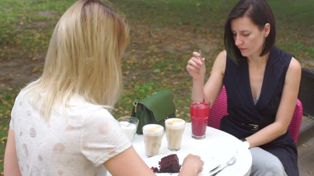 dos niñas están sentados en una mesa en un snack de media tarde - vídeo