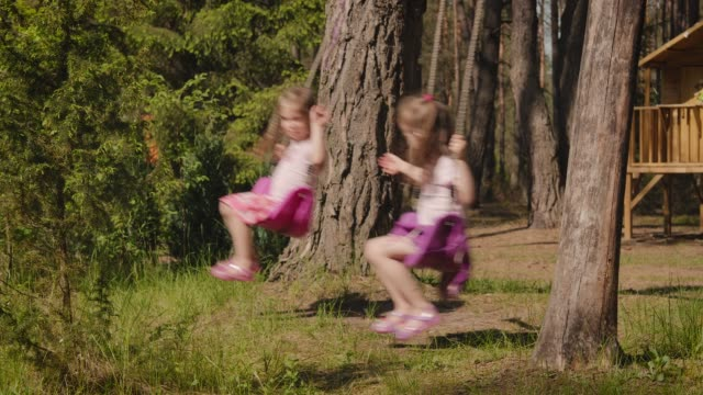two girls are swinging on swings in the forest - gemelle video stock e b–roll