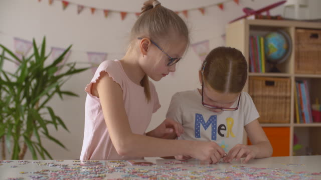 Two girls assembles big bright puzzle at the table