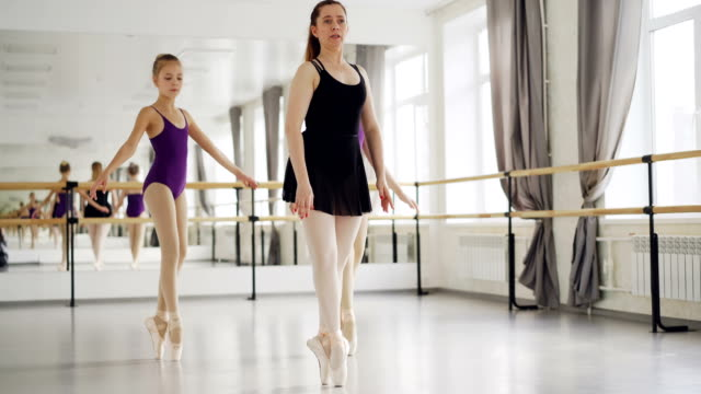 två flickor balettdansare praktiserande dansar på tiptoes med sina erfarna lärare under balett lektion i studio. stor spegel, balett barre och windows är synliga. - på tå bildbanksvideor och videomaterial från bakom kulisserna