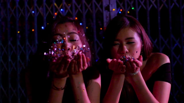 Two girls blowing confetti from hands at a party in   Slow Motion video